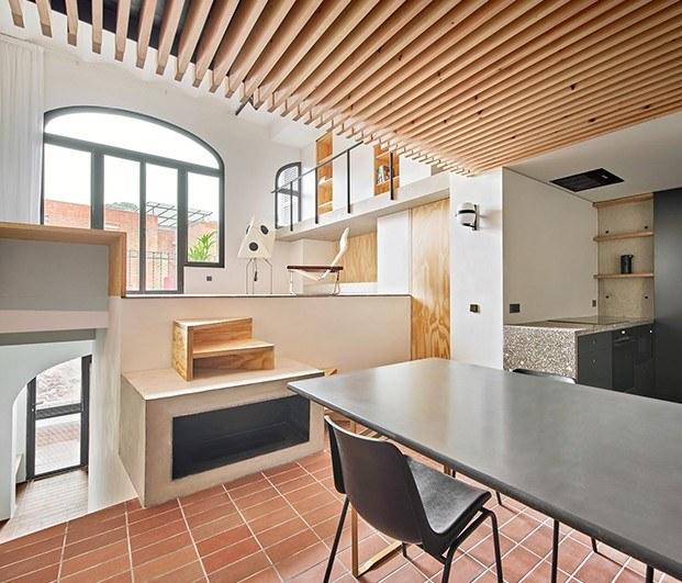 La chimenea preside la zona de comedor de la casa Yurikago y sirve a la vez de peldaño de acceso a la zona de estar