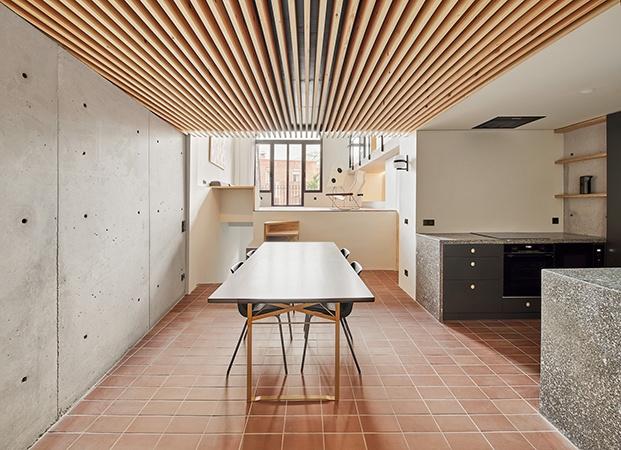 Vista de la cocina y comedor con la escalera de subida al salón y los muros de hormigón visto