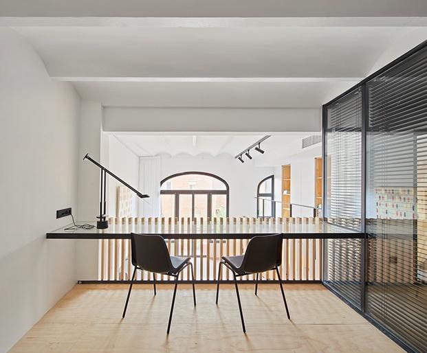 Zona de trabajo asomada al espacio principal de la casa y conectada al dormitorio en la planta alta