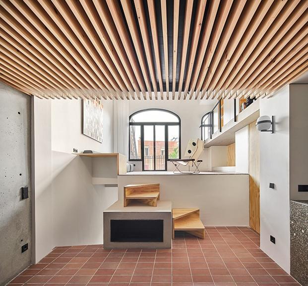 Listones verticales de madera y hormigón. Y una escalera  que sube desde el comedor y cocina hacia la zona de estar de la casa Yurikago