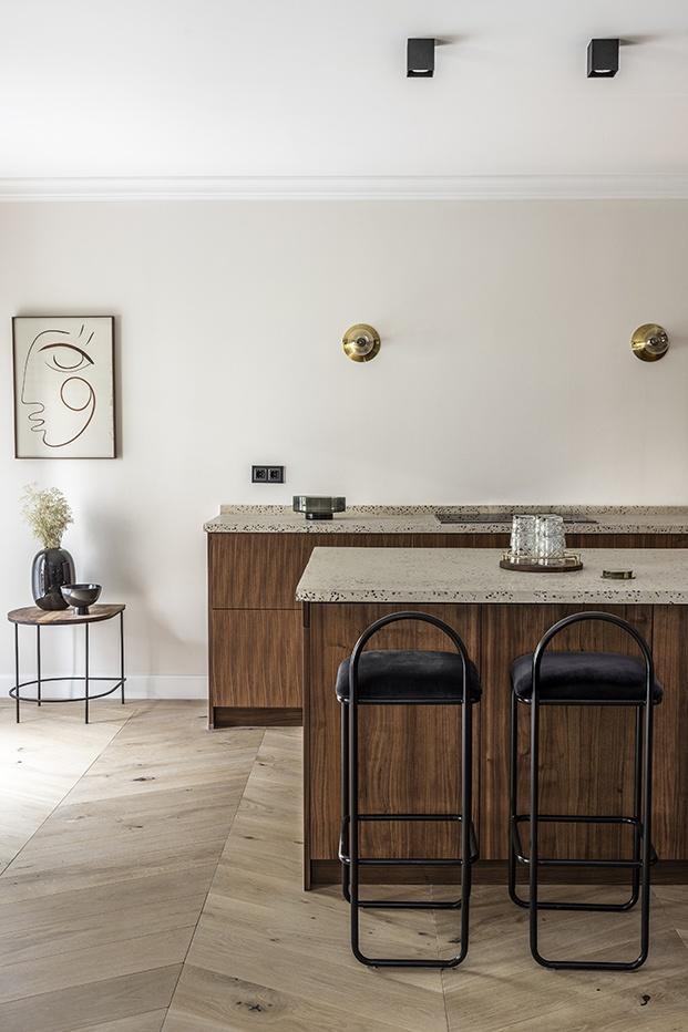 La cocina cuenta con una isla y está realizada con madera y encimera de terrazo