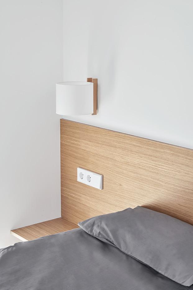 Detalle del cabecero del dormitorio principal que incluye las mesillas, está hecho en roble a juego con el módulo central