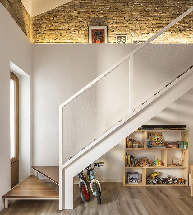 Escalera de acceso al altillo que acoge a los dormitorios. El espacio de debajo se ha aprovechado para los niños
