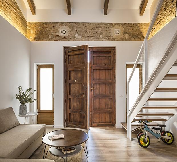 La puerta de entrada de madera y el ladrillo son los originales de la casa transformada en loft en el Cabanyal en Valencia