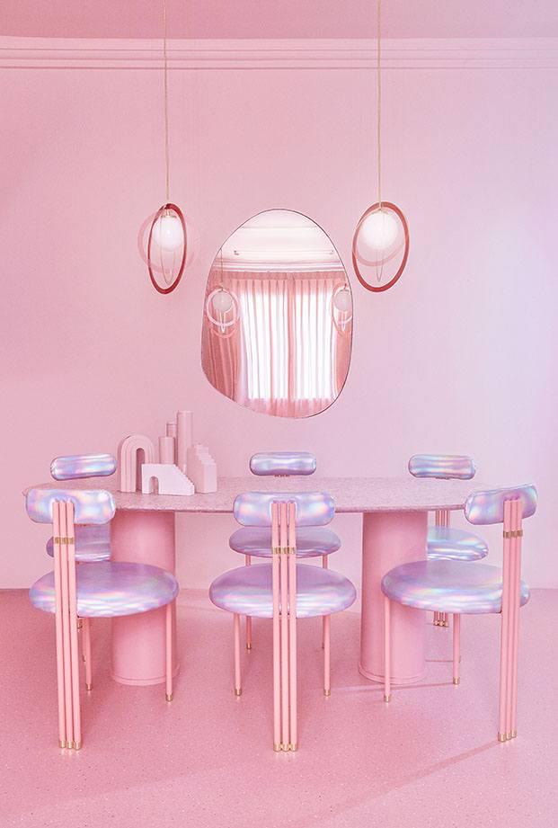 La zona de comedor con mesa y sillas tapizadas con telas iridiscentes y lámparas esféricas