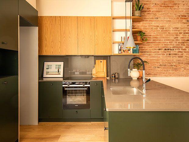 La cocina se integra con la  textura y color, madera de roble para los muebles altos y lacado verde oscuro para los bajos