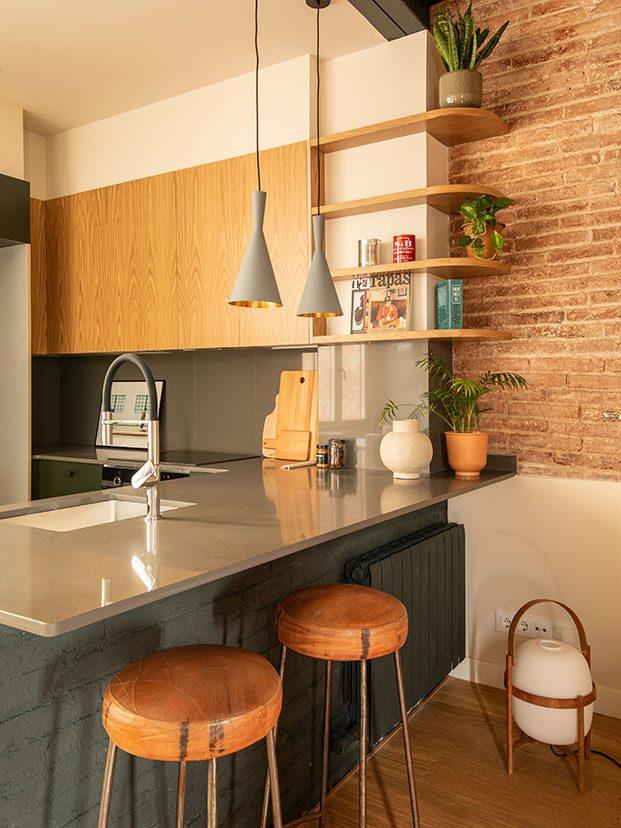 En la cocina, los taburetes altos de piel junto a la barra son de Milesimas. En el suelo lámpara Cesta de Miquel Milá para Santa & Cole.
