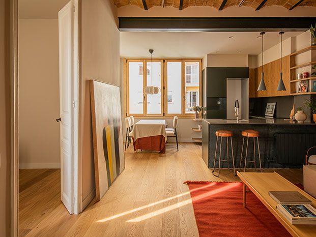 La cocina se encuentra integrada en el centro del espacio y articula la zona de estar y el comedor, al fondo