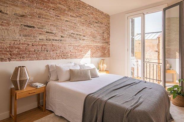 El dormitorio principal está protagonizado por la pared de ladrillo visto rescata en la casa centenaria. Las lámparas son de Felipe Hera