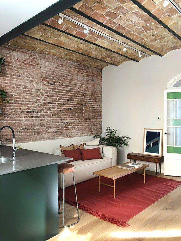Vista en la zona de estar de la casa centenaria en Gràcia de los elementos originales recuperarados el techo de boveda catalana y las paredes de ladrillo