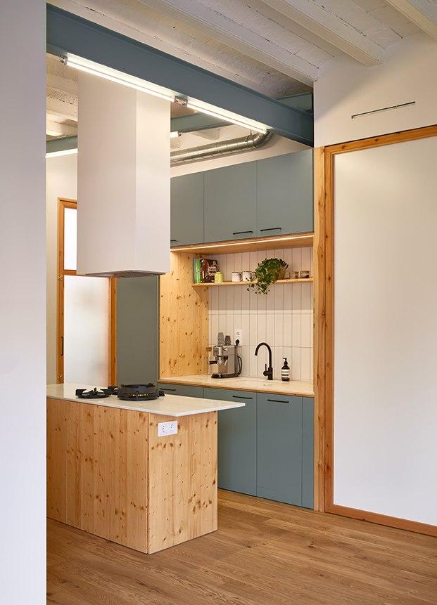 Vista de la cocina con una isla central y potente campana extractora. El mobiliario en blanco, gris y madera