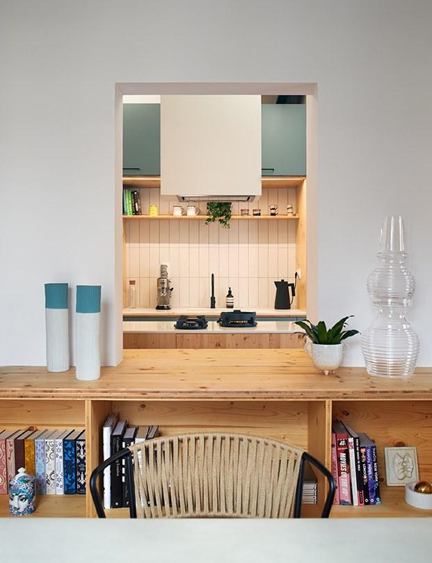 Este hueco abierto en la pared deja que la luz natural entre a la cocina y a la vez sirve de pasaplatos. AL fondo la campana. Y delante el mueble de doble cara que sirve de almacenaje