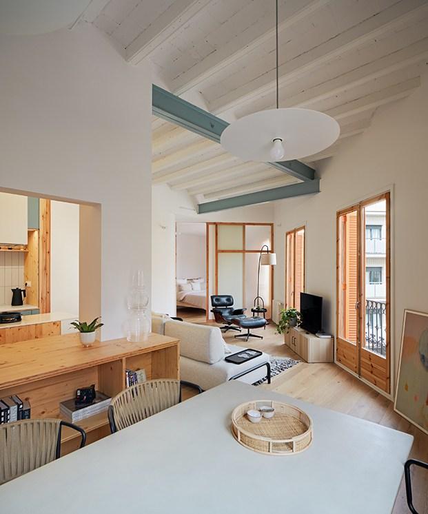 Vista  del apartamento de distribución circular en el que se distinguen desde el comedor, la cocina, la zona de estar del salón y al fondo el dormitorio