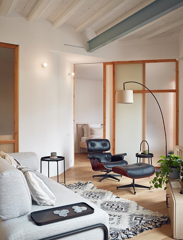 detrás del salón, unos paneles deslizantes ocultan el dormitorio. En primer término, butaca con reposapiés Longue Chair de los Eames que edita Vitra