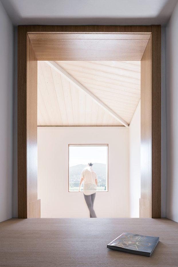 Desde el interior vista de la habitación exterior con carpintería de madera teñida en blanco