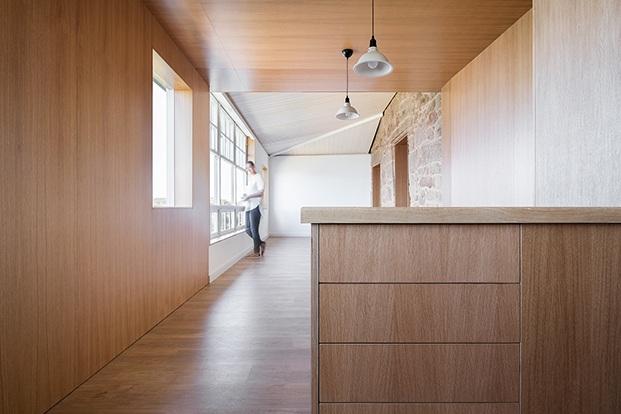 Desde la cocina, vista de la estancia diáfana con grandes ventanales que ilumina a la casa y la conecta con el paisaje