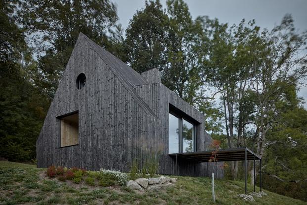 Una cabaña negra con forma de pajarera.
