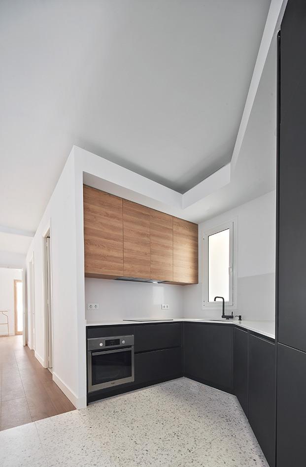 La cocina en esquina decorada en blanco, negro y madera