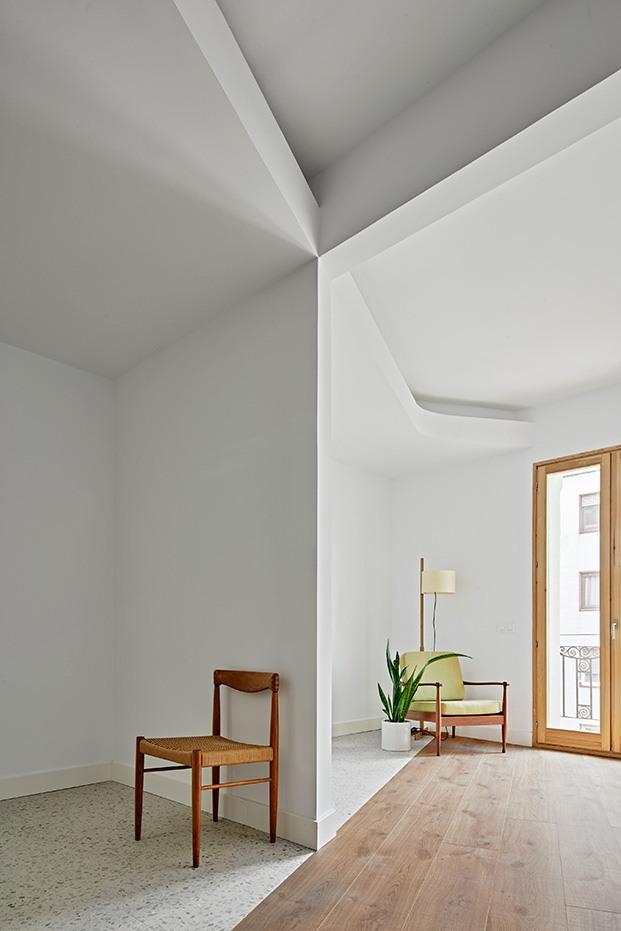 Un muro de carga separa dos de las habitaciones del piso del Ensanche barcelonés. La arquitectura juega con los volúmenes y contrastos en techos y suelos