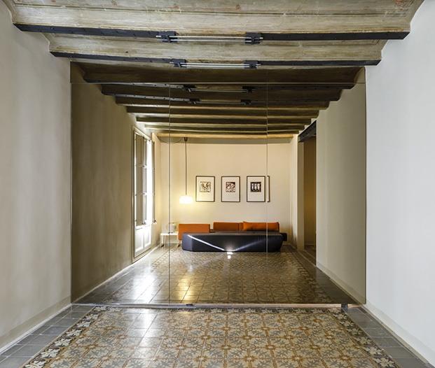 Los  reflejos son parte esencial del proyecto de reforma del piso del Raval Vista de la zona de estar reflejada en las puertas de espejo del dormitorio