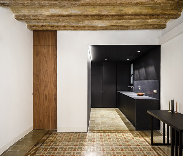 La cocina está en el centro, abierta al comedor y enmarcada en una caja negra