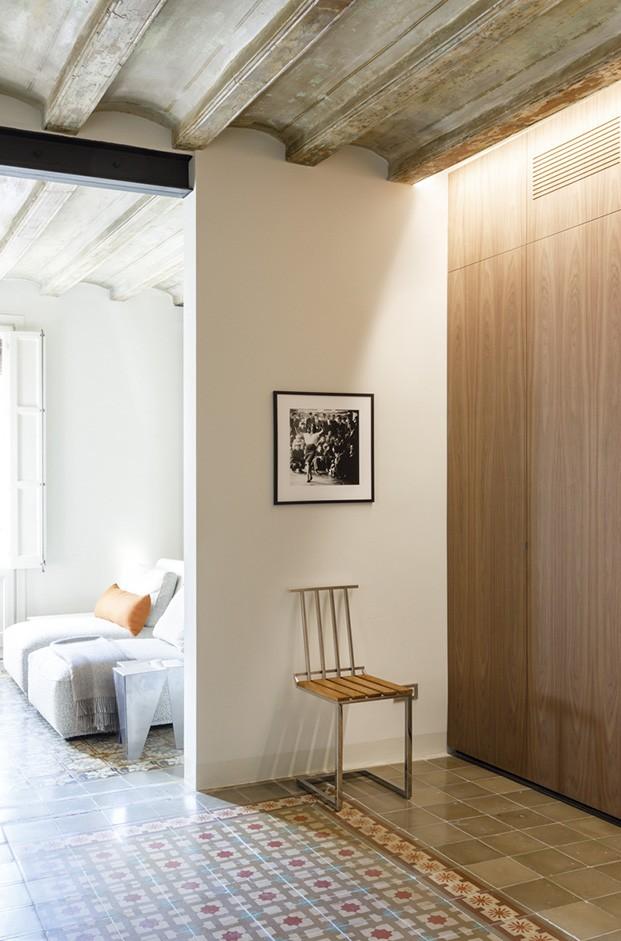 De la zona de estar del salón del piso del Raval está comunicada con una habitación exterior decorada con divanes dedicada al relax y la lectura