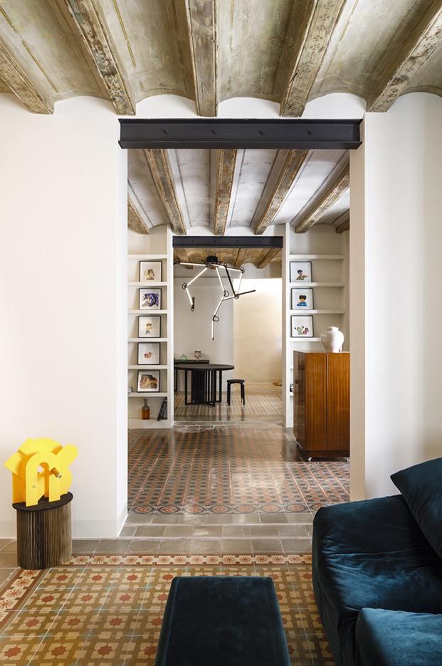 Una secuencia de los espacios encadenados en el piso del Raval: sala de estar, biblioteca y comedor