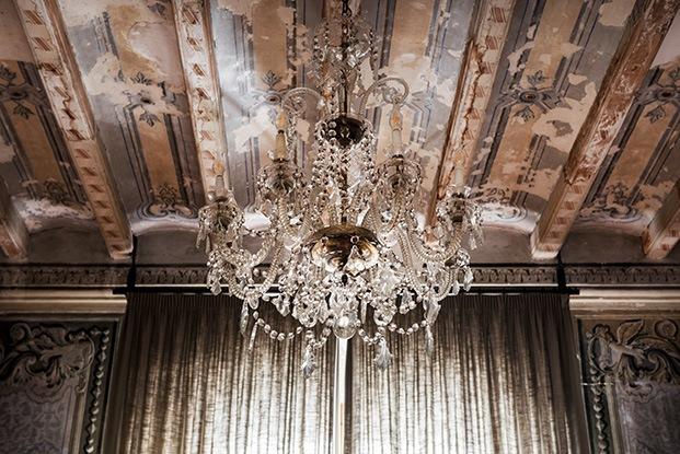 Una clásica lámpara de araña deja ver en el techo de la casa Casclar las pinturas neoclásicas de la planta noble