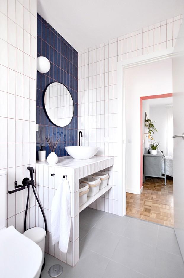El baño esta revestido con azulejos blancos y azules y un espejo de Maisons du Monde