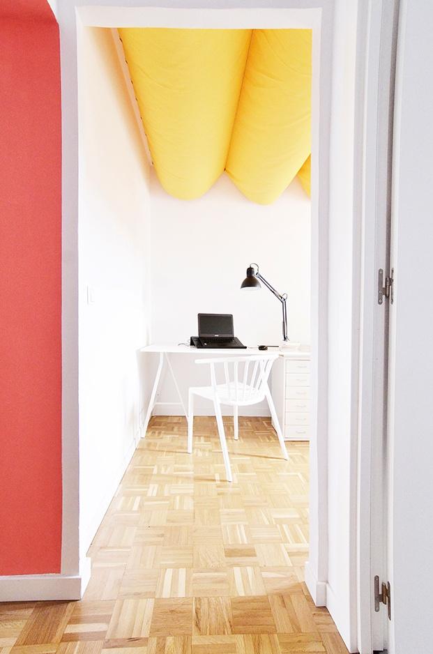 La zona de trabajo del apartamento en Madrid con el techo amarillo insonorizado gracias al techo amarillo fonoabsorbente