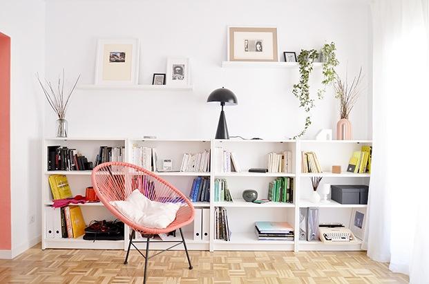 Una estanteria Billy de Ikea, y una silla Acapulco en color coral, en la zona de estar del salón