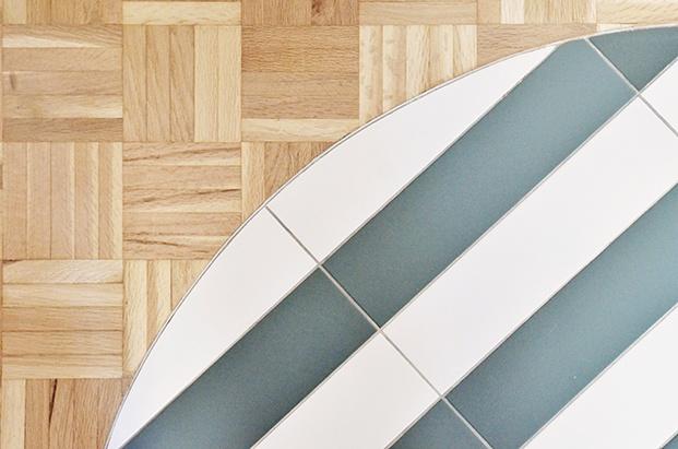 Juegos de materiales en el suelo del apartamento en Madrid. El parqué original recuperado, combina con baldosas cerámicas en la cocina y en la entrada.