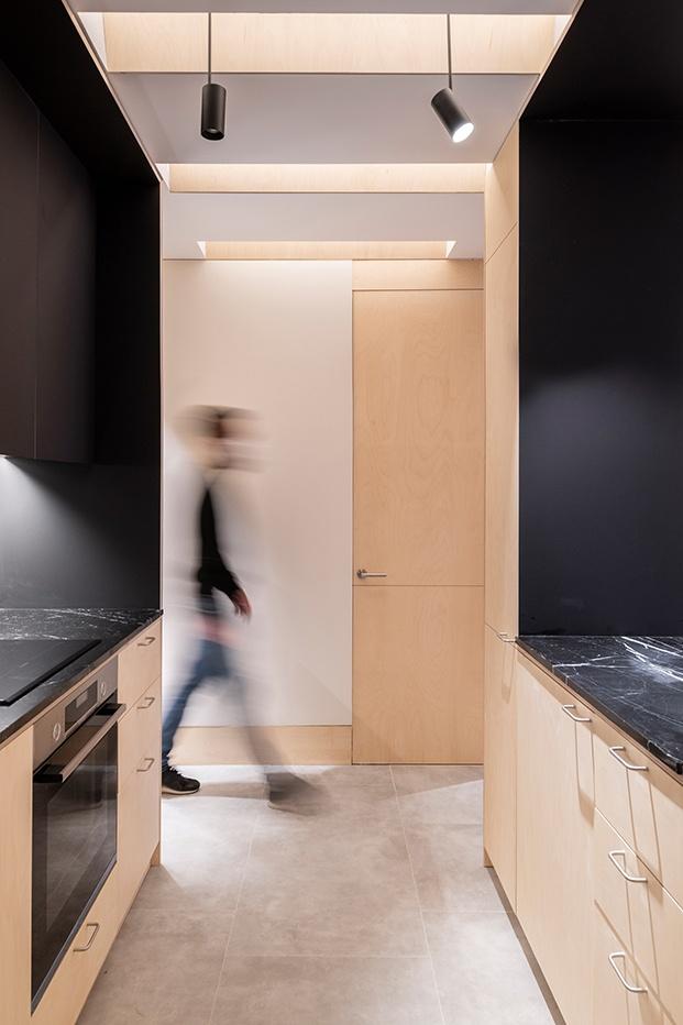 Mármol negro y madera de abedul en la cocina, en el suelo baldosas cementosas
