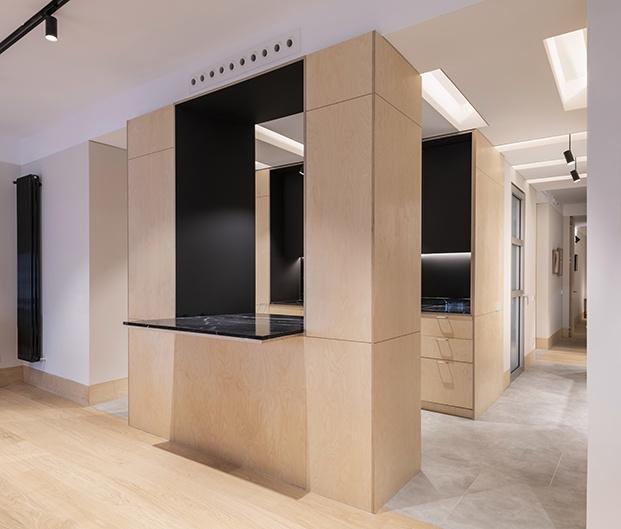 Un mueble de abedul exento diseñado por MINIMO conecta los nuevos espacios de la antigua oficina convertida en vivienda