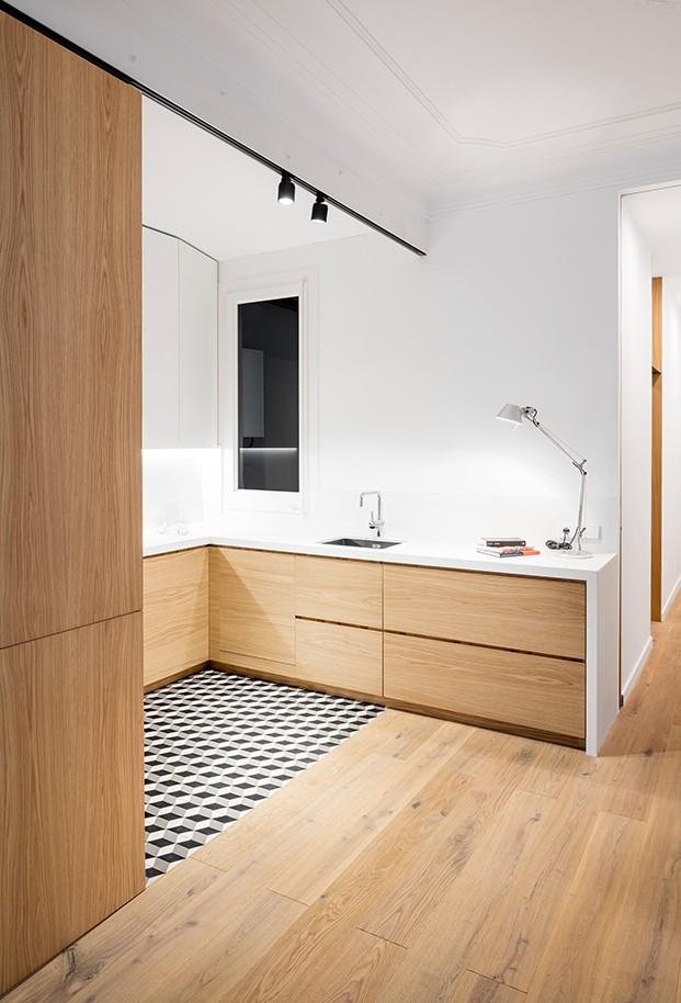 La cocina combina muebles y paviemento de madera de roble, con un suelo de baldosas cerámicas retro