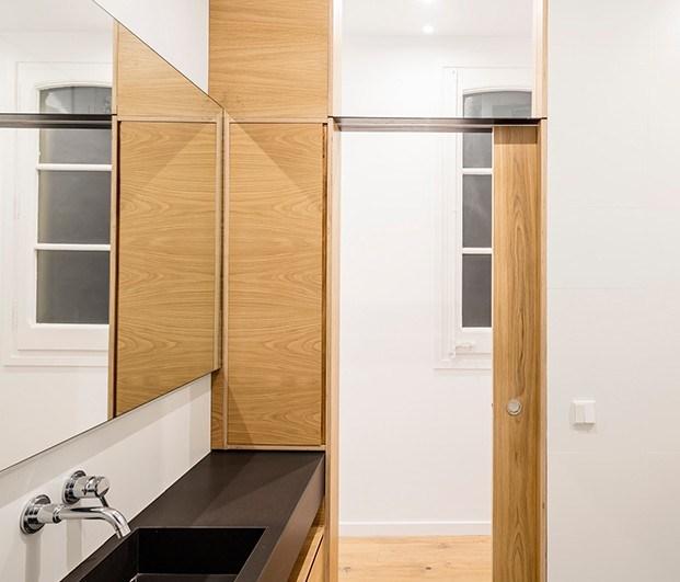 En el baño de este pequeño piso en Barcelona, una ventana superior deja paso a la luz y da amplitud visual