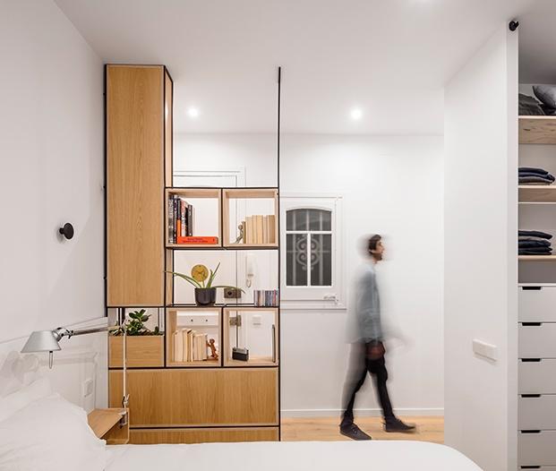 El dormitorio y su zona de armarios. Una estantería abierta diseñada a medida da amplitud visual y permite el paso de la luz