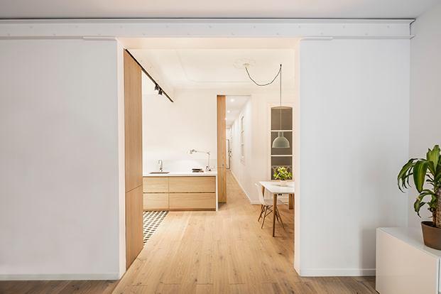 Desde el salón, vista de la cocina y el comedor, con la puerta corredera que lleva al dormitorio y el baño de este pequeño piso en Barcelona.