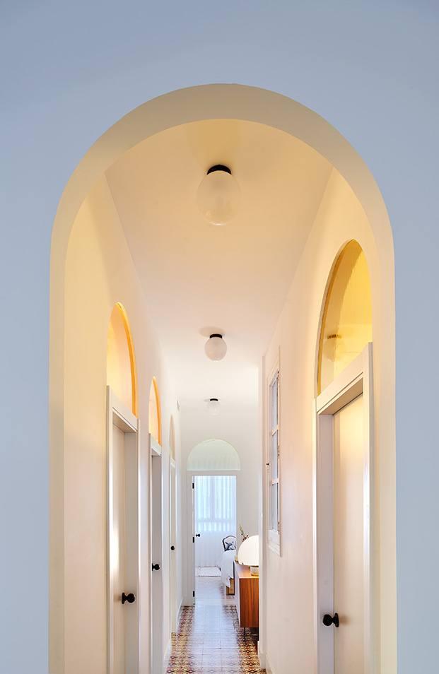 Vista del pasillo y las puertas en forma de arco con sus cristales fijos en ámbar. Al fondo se distingue el dormitorio principal