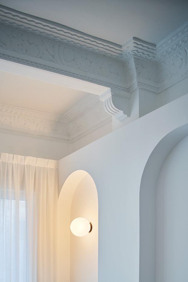 Juegos de geometría, molduras y arcos que recuperan la esencia original de este antiguo piso en Valencia