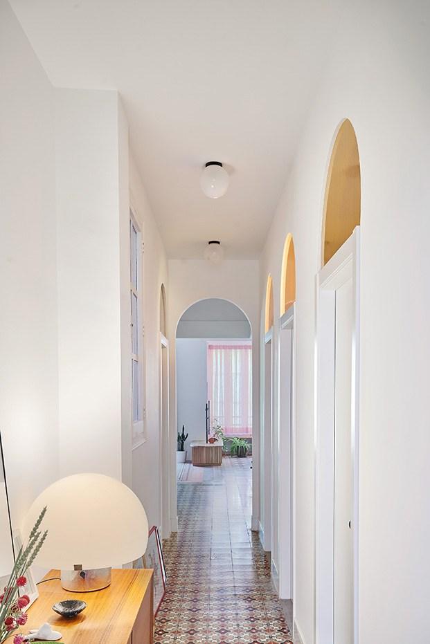 El pasillo que conduce a los dormitorios con arcos y cristales fijos sobre las puertas que dejan pasar la luz