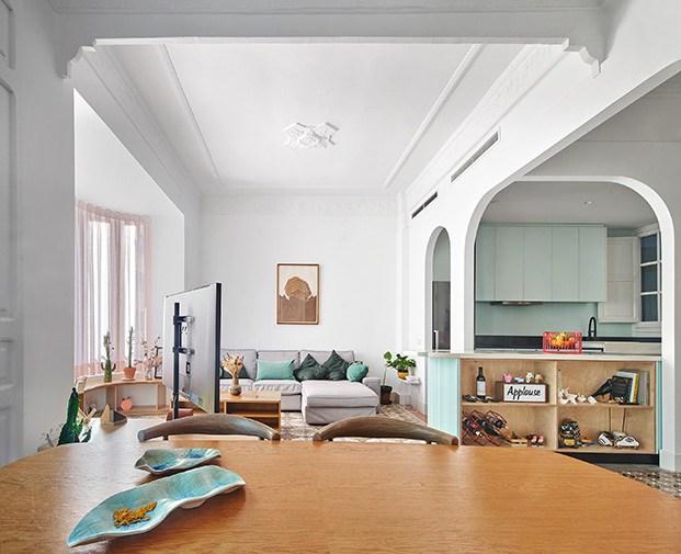 Desde el comedor, vista de la zona de estar del salón, y al fondo la cocina de este antiguo piso en Valencia que ha recuperado su esencia