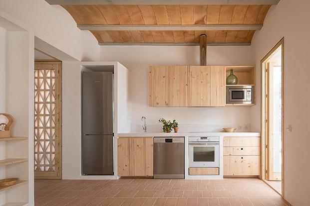 La cocina con mobiliario de madera, y encimera de Corian. El techo de bovedilla mallorquin y el suelo de baldosas de terracota prensada