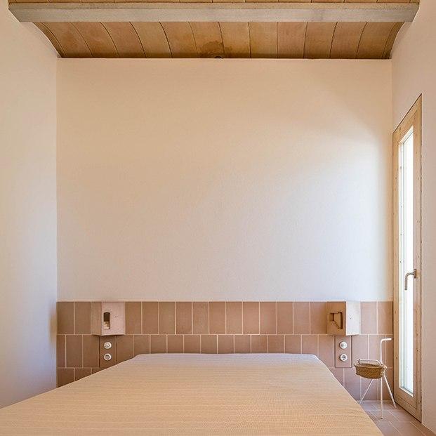 En el el dormitorio se ha realizado un cabecero de obra con baldosas cerámicas y luminarias, diseño de Marià Castelló integradas