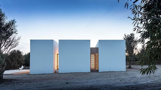 Vista de los volúmenes en los que se ha divido esta pequeña casa de campo en Formentera, delante el aljibe que sirve de terraza