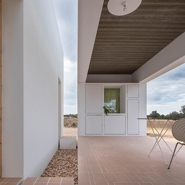 Vista del porche decorado con piezas diseño de los arquitectos para Diabla y sillas Tom Vac de Ron Arad que edita Vitra