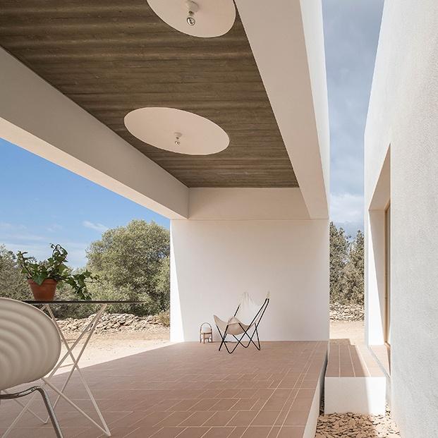 Sillas Tom Vac de Ron Arad para Vitra, mesa D12, diseño de Marià Castelló para Diabla y una BKF, silla Butterfly, junto a una lámpara Cestita de Miguel Mila para Santa&Cole