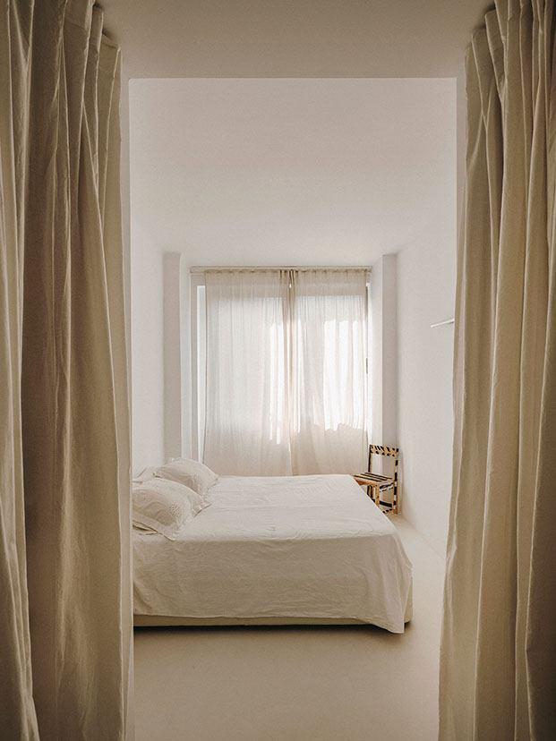 El dormitorio  de la pareja, limpio y depurado, en la esquina una silla de Marc Morro