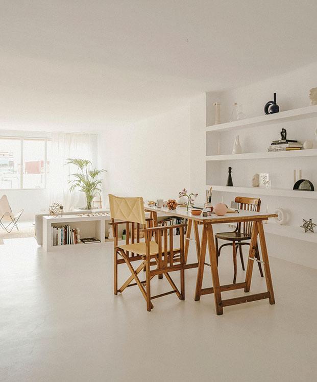 Estanterías de obra en blanco y una mesa con caballetes protagonizan el estudio de Valeria Vasi