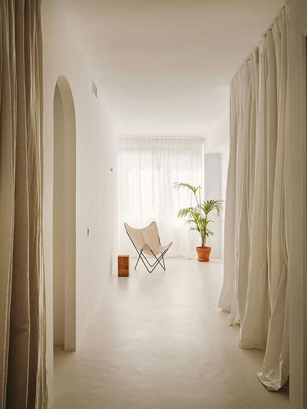 Un arco da paso a la zona de armarios cubierta con cortinas